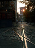 Dumbo Tracks, Brooklyn, New York USA. The setting sun pokes through an eye of the Brooklyn Bridge to highlight the railway tracks on old cobblestoned Plymouth royalty free stock photography