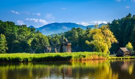 Dumbrava, Sibiu, Romania: Paesaggio di un lago con il mulino a vento Immagine Stock
