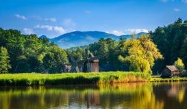Dumbrava, Sibiu, Rumania: Paisaje de un lago con el molino de viento Imagen de archivo