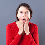 Dumbstruck young woman with jaw dropping expression touching her face Royalty Free Stock Photography