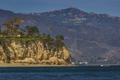 Dume Cove Beach. Secluded Dume Cove beach and tall cliffs with Santa Monica Mountains in the background, Malibu, California Royalty Free Stock Photo