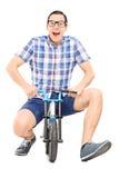 Dummer junger Mann, der ein kleines kindisches Fahrrad reitet Stockbild