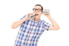Dummer Mann, der mit durch Blechdosetelefon spricht Stockbilder