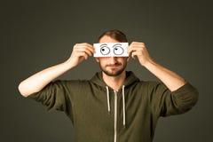 Dummer Mann, der mit Hand gezeichneten Augenbällen schaut Stockbilder