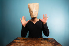 Dummer Mann mit Tasche über seinem Kopf und Händen oben Lizenzfreies Stockfoto