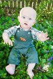 Dummes Baby, das unter Blumen sitzt Stockfoto