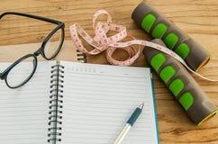 Dummkopf, messendes Band, Gläser mit Tagebuch buchen lizenzfreie stockfotos