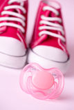 Dummy and baby shoes Stock Image