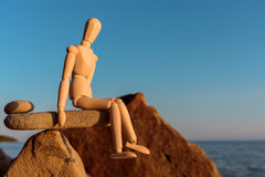Dummy in balance. Wooden dummy in balance on the stone on seashore royalty free stock photography