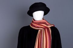 Dummy in hat, coat and scarf. Female mannequin dressed in black headgear, overcoat and scarf. Women autumn fashion look Stock Images