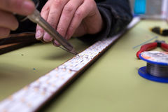 Dummy manufacturing workroom. Worker creating a straight line of led bands Stock Photo