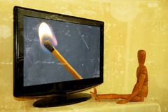 Dummy painter in front of television with lit match Stock Images