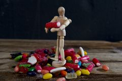 Dummy puppet holding and carrying sweet candy upon pile of licorice and caramel gummies. Representing sugar addiction and unhealthy nutrition lifestyle concept Royalty Free Stock Image