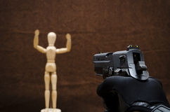 Dummy shot. Aiming a handgun on a figureine Stock Photography