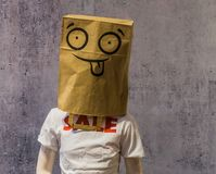 Dummy wearing a funny paper bag on its head and a t-shirt with Sale on it, shopping discount concept stock photo