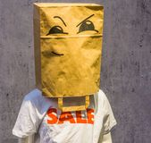 Dummy wearing a funny paper bag over its head with a angry face on it, T-shirt saying sale, shopping discount concept stock photography