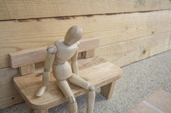 Dummy wood man acting alone wooden chair Stock Photos