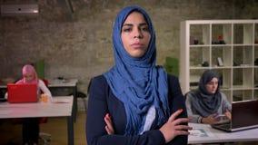 Dumna i ufna arabska kobieta w zmroku - błękitny hijab patrzeje prosto przy kamerą podczas gdy trwanie cisza z jej ręką dalej