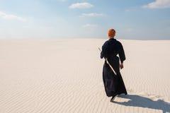 Dumny mężczyzna, wojownik chodzi przez pustkowia w distanc Obrazy Royalty Free