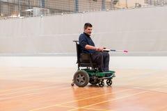 Dumny niepełnosprawny mężczyzna pokazuje z hokejowym kijem na elektrycznym wózku inwalidzkim bawić się sporty IWAS - Międzynarodo zdjęcia royalty free