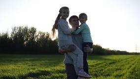 Dumny ojciec dwa dziewczyny w naturze Niesie one w jego rękach słońce błyszczy młoda dziewczyna wysyła lotniczych buziaki zbiory