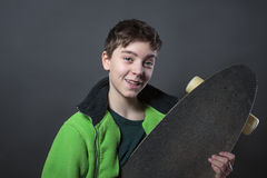 Dumny uśmiechnięty nastoletni chłopak trzyma jego długa deska Obraz Royalty Free