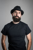 Dumny ufny brodaty modniś jest ubranym czarną koszulkę i kapeluszową patrzeje kamerę obrazy stock