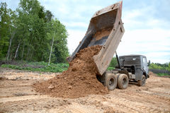 Dump-body truck unloads a ground Stock Images