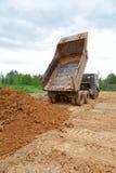 Dump-body truck unloads a ground Royalty Free Stock Photos