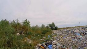 Dump bordered by green grass. Green grass is slowly opened with garbage from a landfill stock footage