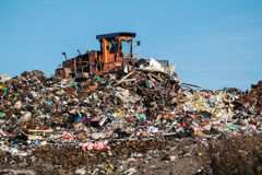 The dump and the bulldozer. Bulldozer moves the dump on the waste site Royalty Free Stock Photography