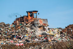 The dump and the bulldozer. Bulldozer moves the dump on the waste site Royalty Free Stock Photo