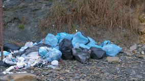 Dump garbage bags in nature near mountains environmental pollution. Dump garbage bags in nature near mountains. Environmental pollution outdoors and ecological stock video footage