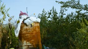 Dump near the road. Garbage dump in a rusty barrel next to the road stock footage