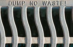 Dump No Waste Grate. Iron storm sewer grate reading DUMP NO WASTE! which empties excess rain water from the street into the river stock photos