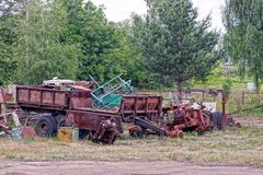 Old rusty machinery and parts in the yard in the grass and vegetation stock photo