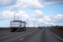 Dump tipper semi truck with two trailers on wide highway Royalty Free Stock Images