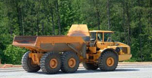 Dump truck. Side view of modern industrial dump truck on road construction site with trees in background Royalty Free Stock Image