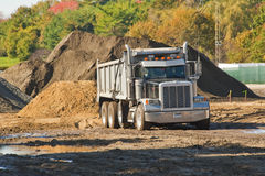 Dump truck. A dump truck about to unload a pile of dirt at an excavation site Stock Photo
