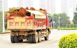 Dump truck. Overloaded dump truck driving at road Stock Photo