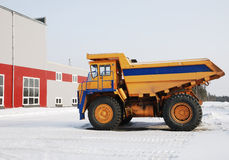 Dump-truck. Heavy yellow dump-truck near industrial building in winter Royalty Free Stock Photos