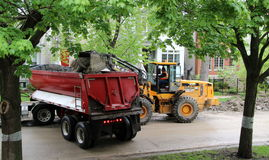 A dump truck accepts dirt and rocks from a wheeled bulldozer on a Chicago residential. Workers operate a dump truck and a wheeled bulldozer heavy equipment on a Royalty Free Stock Photos