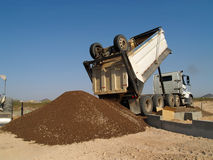 Dump truck backed up dumping dirt Stock Images