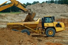 Dump Truck Being Loaded. By an excavator arm stock images