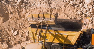 Dump truck being loaded with soil by shovel. Construction machinery working at the construction site stock video footage