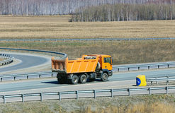 Dump truck. Big yellow dump truck on the country highway Royalty Free Stock Photography