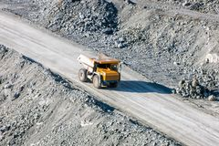 Dump truck at the quarry. Dump truck at the bottom of stone pit stock image