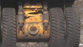 dump truck Caminhão de mineração As rodas enormes de um caminhão de passagem à máquina escavadora na carga da raça Um caminhão gi filme
