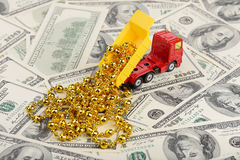 Dump truck and christmas toys on the dollars background. (installation on the theme of New Year and Christmas business Stock Image