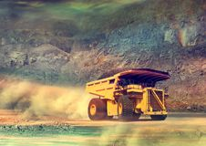 Dump Truck Drove in the Mining Area. Mining Activity - Dump Truck Drove in the Mining Area bring raw materials, through steep hills and dusty ground Stock Photos